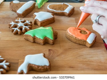 Women decorates christmas cookie. Some cookies are decorated. Wooden background.