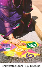 Women decorating and coloring tradition colourful rice,sand art (Rangoli) on the floor with paper pattern using dry rice and dry flour with colored from natural pigments like sindoor, haldi (turmeric)