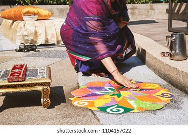 Women decorating and coloring tradition colourful rice, sand art (Rangoli) on the floor with paper pattern using dry rice and dry flour with colored from natural pigments like sindoor, haldi (turmeric