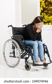 Women with disability. Depressed young women sitting at the wheelchair and covering her face with hands