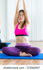 Women doing back and arms stretching yoga pose, sitting on mat in fitness gym group class. Healthy lifestyle and wellness concept.