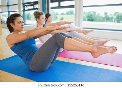 Women doing boat pose in yoga class in fitness studio