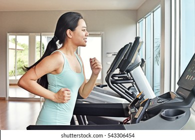 Women doing cardio exercises, running on treadmills in the gym