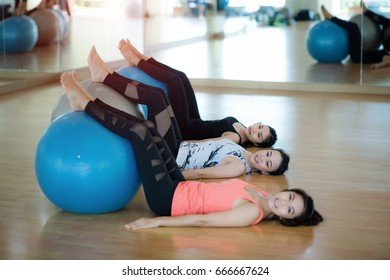 Women doing exercise in group with fit ball in gym or yoga class