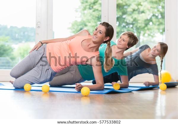 Frauen, die im postnatalen Regressionskurs Übungen für Beckenboden durchführen