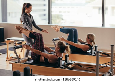 Women doing pilates exercises lying on pilates workout machines while their trainer guides them. Two fitness women being trained by a pilates instructor.