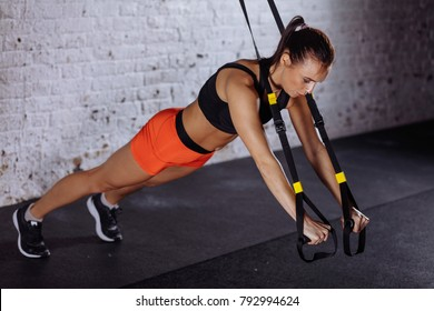 Women doing push ups training arms with trx fitness straps in gym
