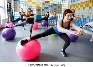 Women doing squats on a fitness ball in the gym. Selective focus.