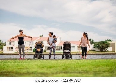 Women doing workout in park bringing their kids in strollers. Young mothers doing stretching exercise using stretch banks in park beside a lake.