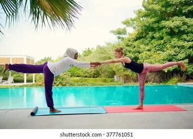 Women doing yoga by the poolside in Dubai