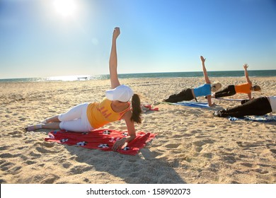 Women doing yoga exercise  Salamba Kapotasana or Supported Pigeon Pose on an empty beach