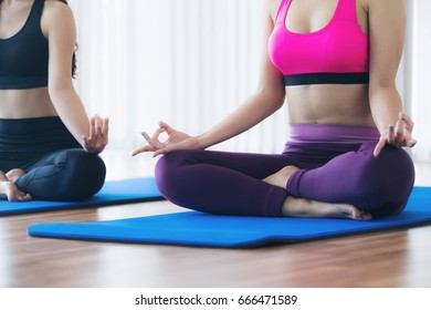 Women doing yoga lotus pose, sitting on mat in fitness gym group class. Healthy lifestyle and wellness concept.