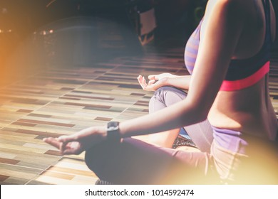 women doing Yoga meditation in public fitness gym.