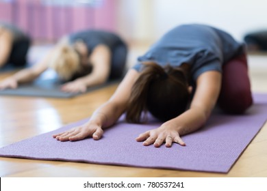 Women doing yoga training together and performing the child's pose on a mat, healthy lifestyle and fitness concept