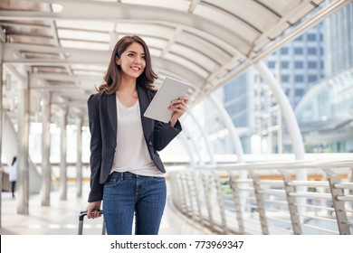 Women are Dragging their luggage in a Smartphone. See Mobile Travel Maps. During the Trip to the airport.Businesswoman Using Smart Phone Ordering Taxi on app,Taxi Service through Secret concept