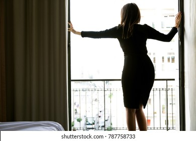 Women dressed in black standing. Woman from the back wearing high heels. Girl standing and posing in bedroom. Getting ready to go out.