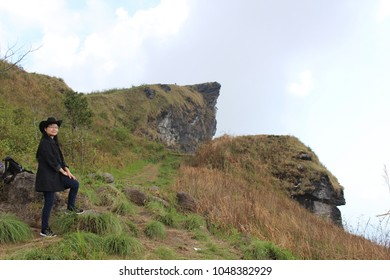 Women dressed in black and wearing a black hat standing on  steep walkway on the mountain. and on the highest point of the high  mountain. Phu Chee FAH national forest park  in Chiangrai,Thailand