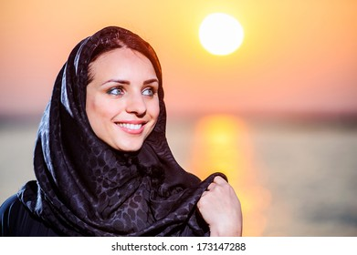 Women dressed middle eastern way poses on sunset background.