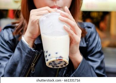 Women drink pearl milk tea through a straws.