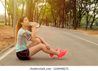 Women are drinking cool water in the park and woman listening to music on running Belt.
