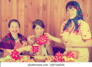 Women drinks tea with pancake during  Shrovetide