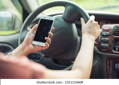 women driver with a cell phone in hand while driving