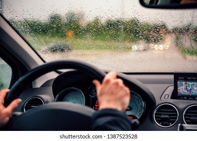 Women driving car with windshield covered with raindrops