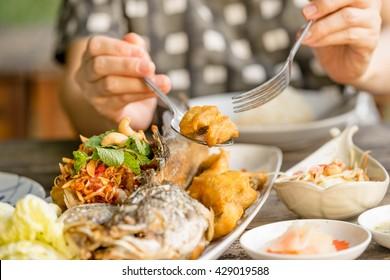 women eating fried fish in restaurant