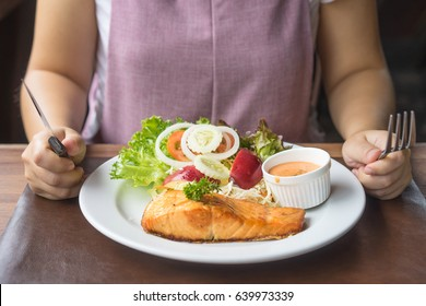 women eating salmon steak on white plate on table hand holding knife and fork