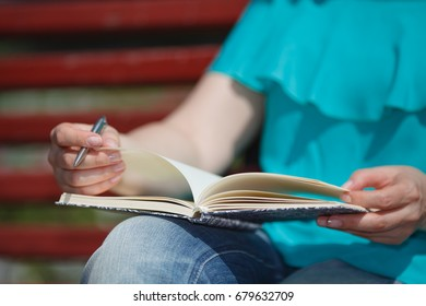 women and education, close up of hands of girl studying for college exam in park. Side view