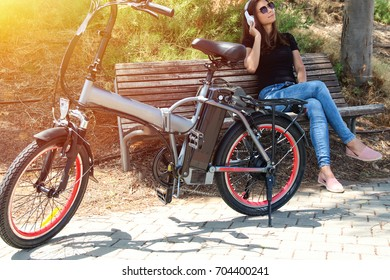 Women  with electric bicycle sitting in the park with headphone