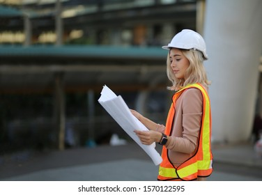 The women engineer holding blueprints standing against  building. The concept of engineering, construction, city life and future.