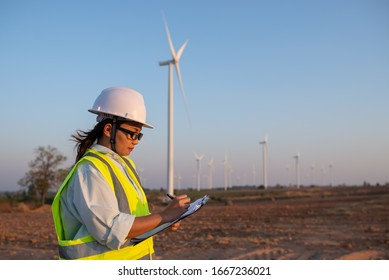 women engineer working and holding the report at wind turbine farm Power Generator Station on mountain,Thailand people