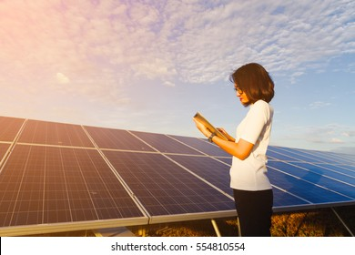 women engineer working on checking equipment at green energy solar power plant: checking solar panel and structure with tablet checklist