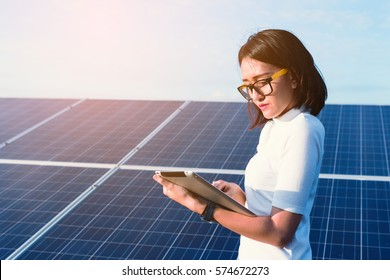 women engineer working on checking checking status equipment at solar power plant with tablet checklist; woman working on outdoor at solar power plant
