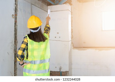 Women Engineering wearing yellow helmet and working at construction site