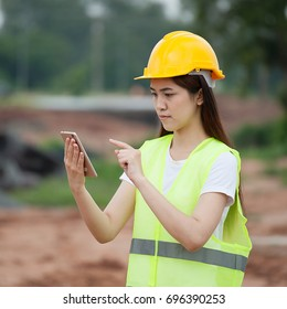 Women engineers using smart phone in a construction site