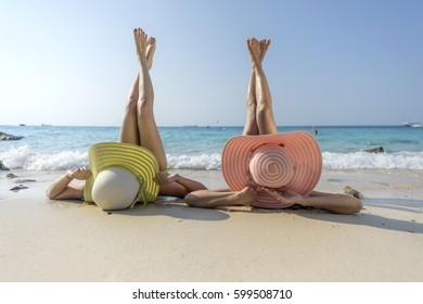 women enjoy the sea by laying down on sand of beach wearing millinery hat, and both legs up in the air