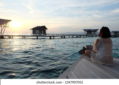 Women enjoy the sunset on the edge of the cottages at Pulo love Gorontalo Indonesia resorts