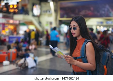 Women enjoy traveling on the map to the train station. Holiday travel ideas.