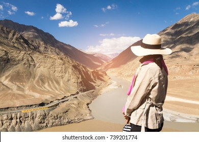 Women enjoying life with river view of Sindhu (Indus) and Zanskar Rivers; these two lines are different shades of color in summer Himalayas, Ladakh, India.