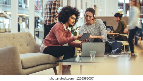 Women entrepreneurs sitting in a lounge at work place sharing ideas using tablet and laptop. Businesswomen in a meeting discussing work in office.