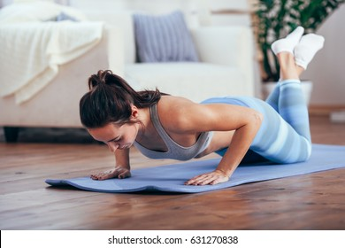 women exercise indoor at home she is acted push-ups
