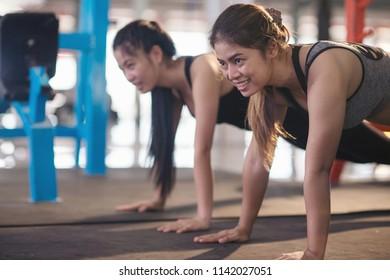 Women exercising on floor in fitness gym