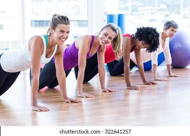 Women exercising on floor in fitness studio