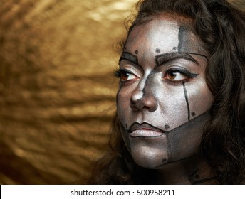 women face with metal mask body art on golden background
