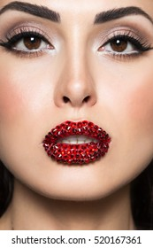Women face with Swarovski crystals on lips. Brunette woman with fashion hairstyle and Holiday Make-up with red gems.