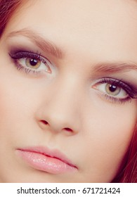 Women facial look. Close up of pretty female face with beauty eyes make up. Dark eyeshadow and long black lashes.