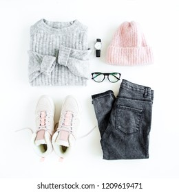 Women fashion clothes and accessories. Feminine youth collage on white background top view. Flat lay female style look with warm sweater, jeans, cap, sneakers, glasses. Top view.