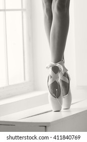 Women feet in pink pointe shoes with a bow are dancing on tiptoes
